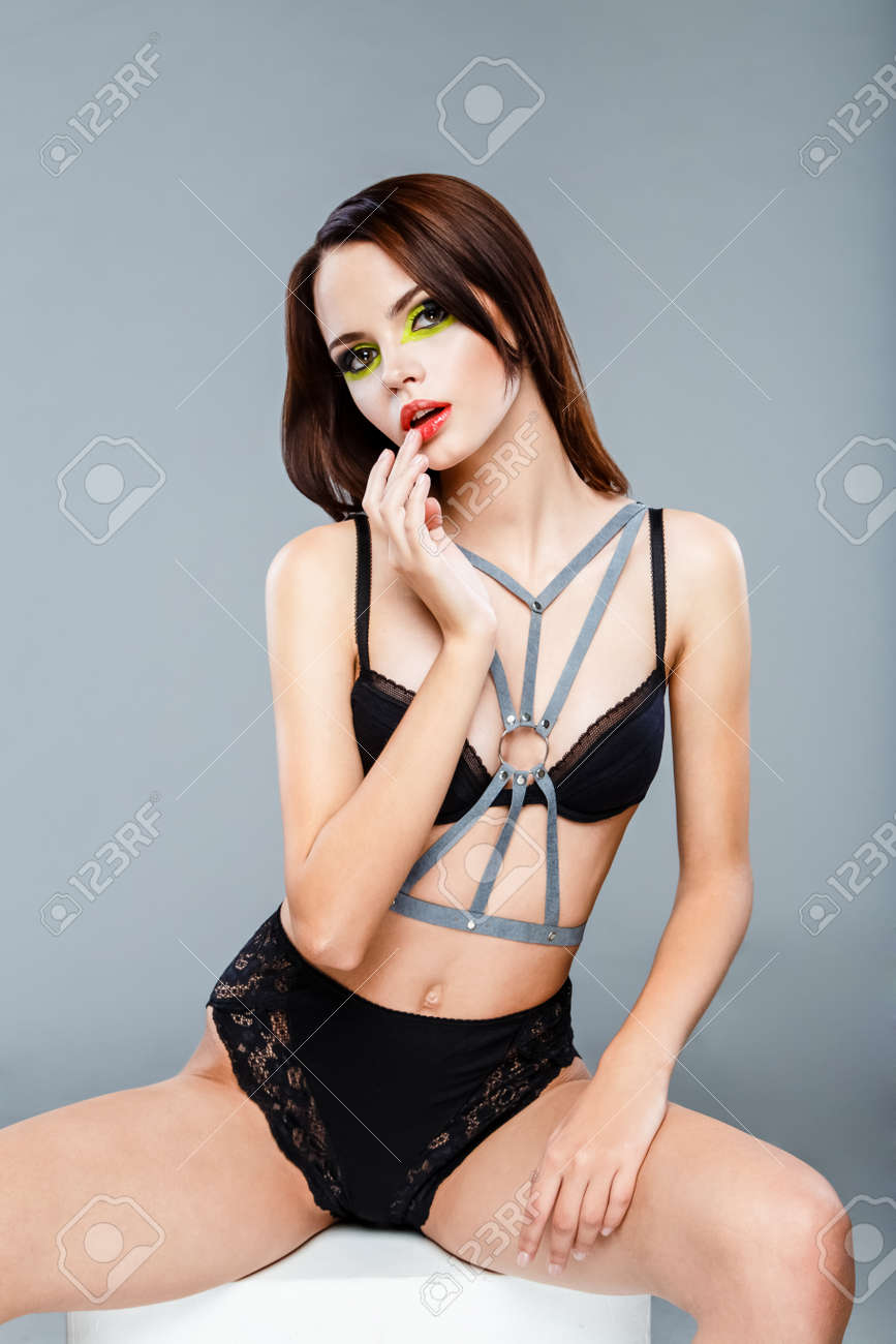 4e699e897fe81 Sexy young woman wearing black lingerie with bra and panties with bright  make up posing in
