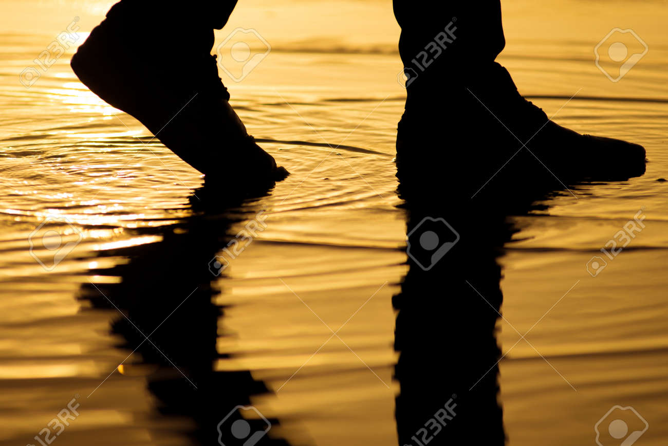 Man walking on the water surface with silhouette legs reflection - 30148270