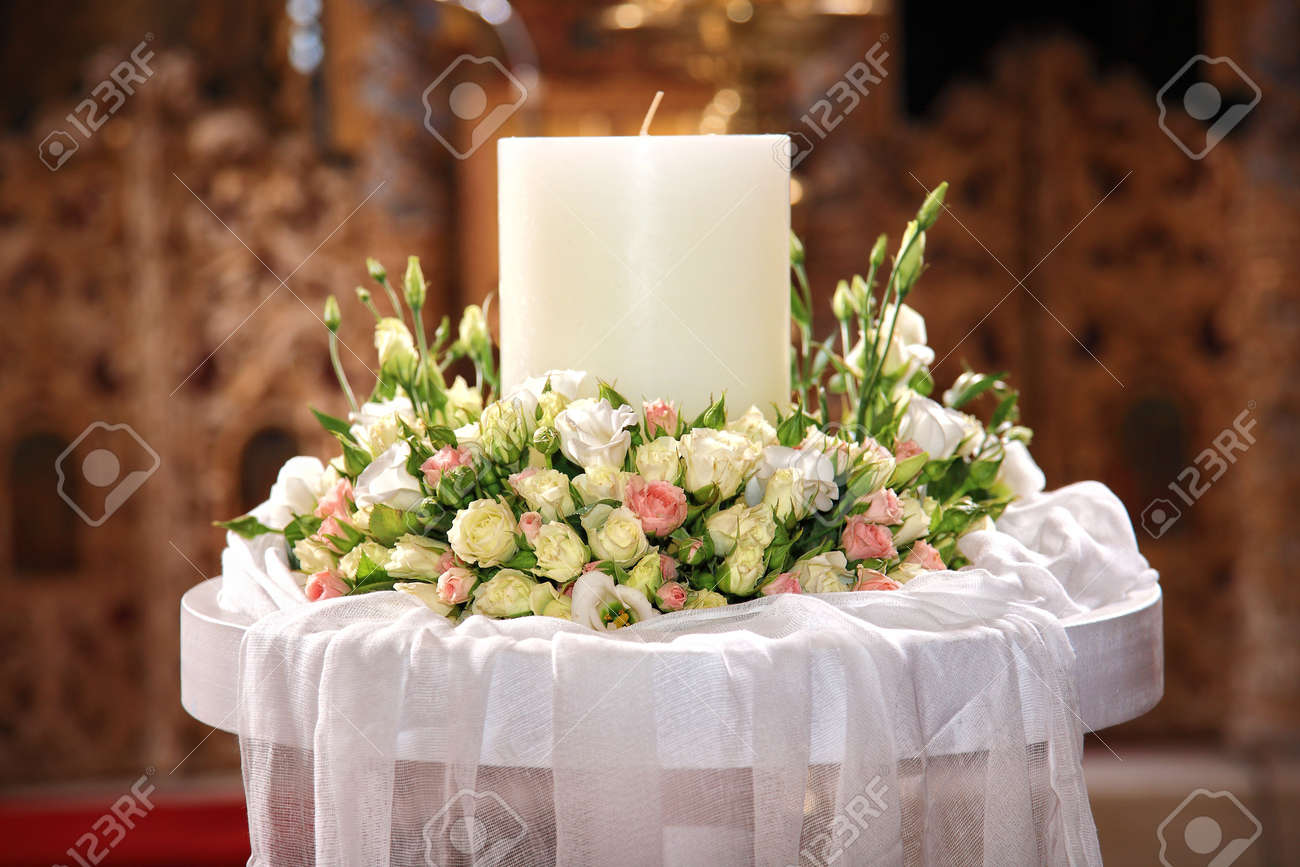 close-up of flowers and a big candle on a greek wedding