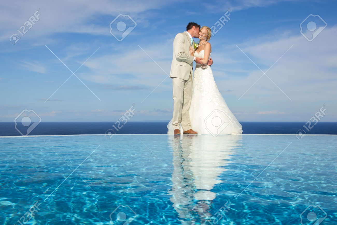 portrait of a bride and groom kissing on a infinity pool against the sky - 34901659