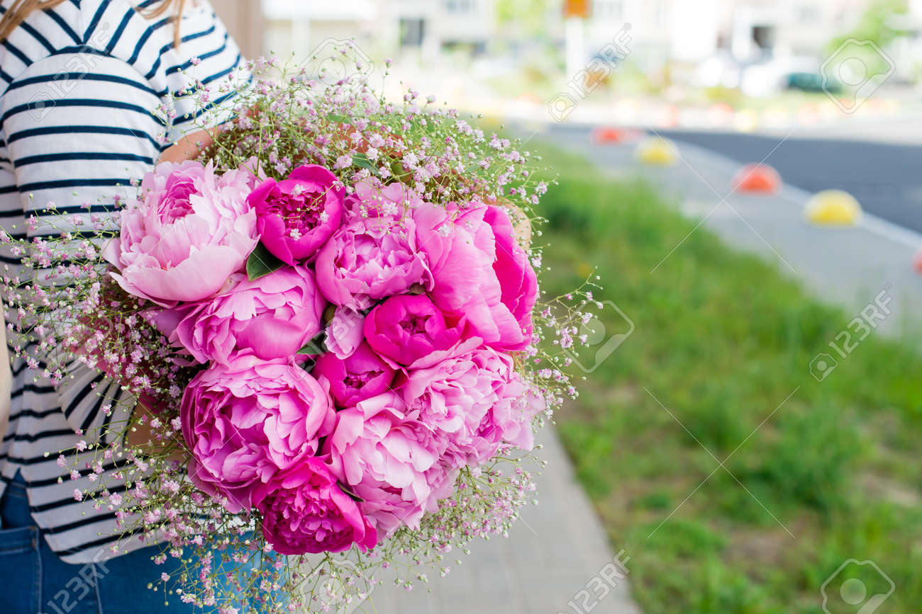 Woman holding beautiful bouquet of pink peonies and little white stock photo woman holding beautiful bouquet of pink peonies and little white flowers wrapped in paper in the street symbol of romantic moment izmirmasajfo