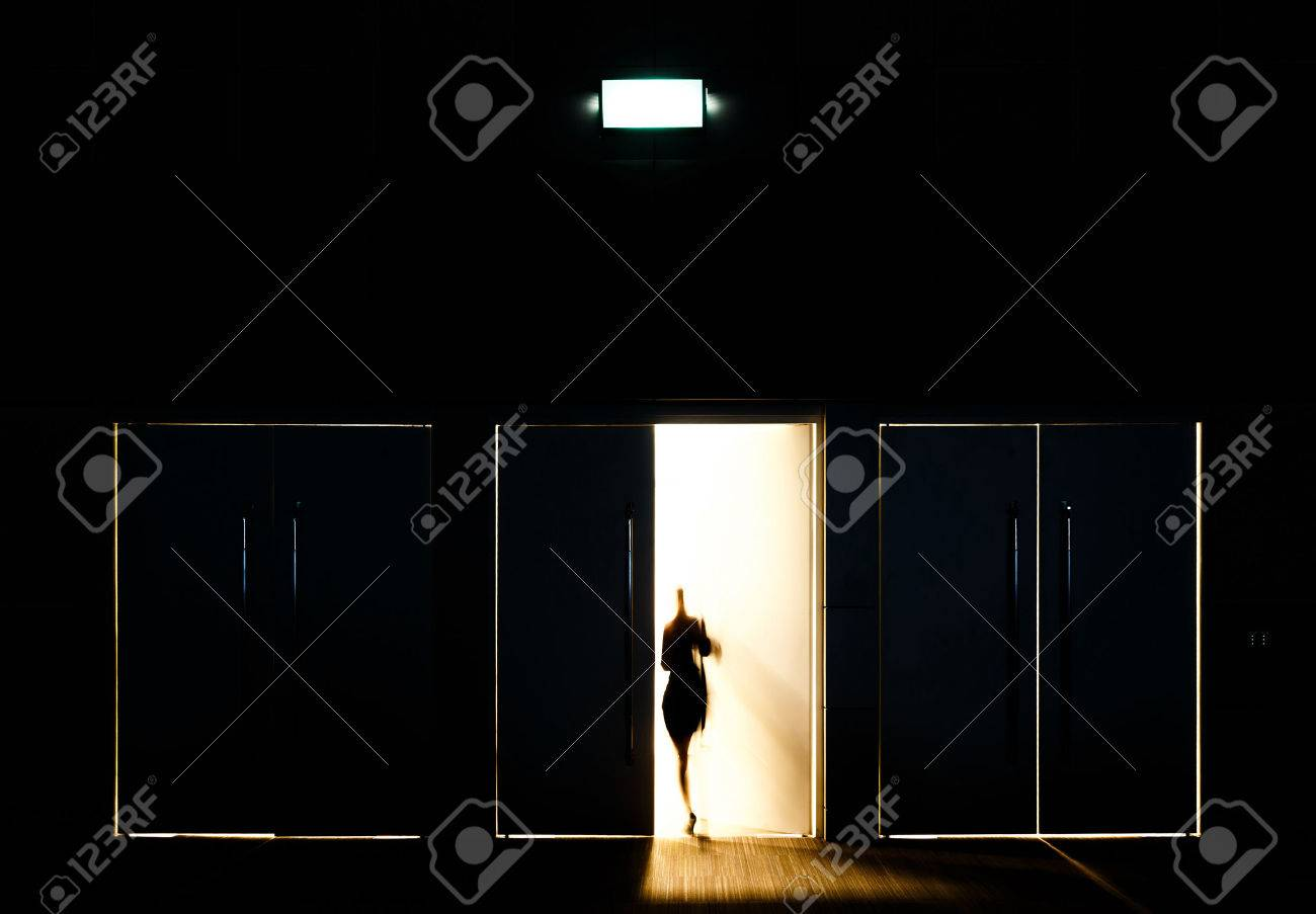 Door opened with motion blur of a man and light coming through the space - 32248227