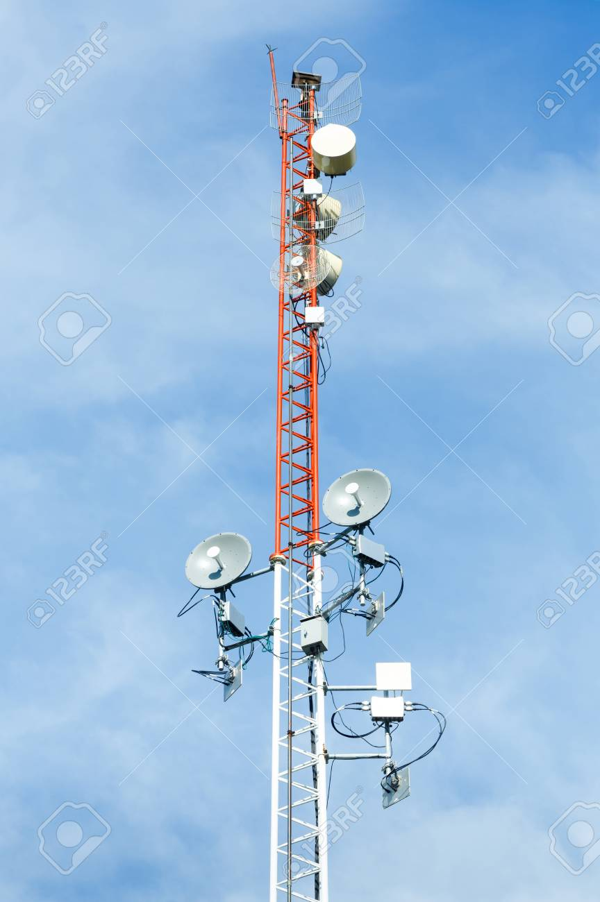 White and red color antenna repeater tower on blue sky, telecommunication