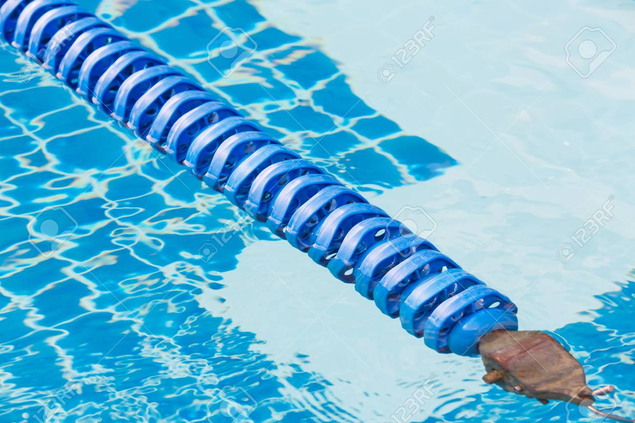 Blue color plastic swimming pool lane rope floating on water..
