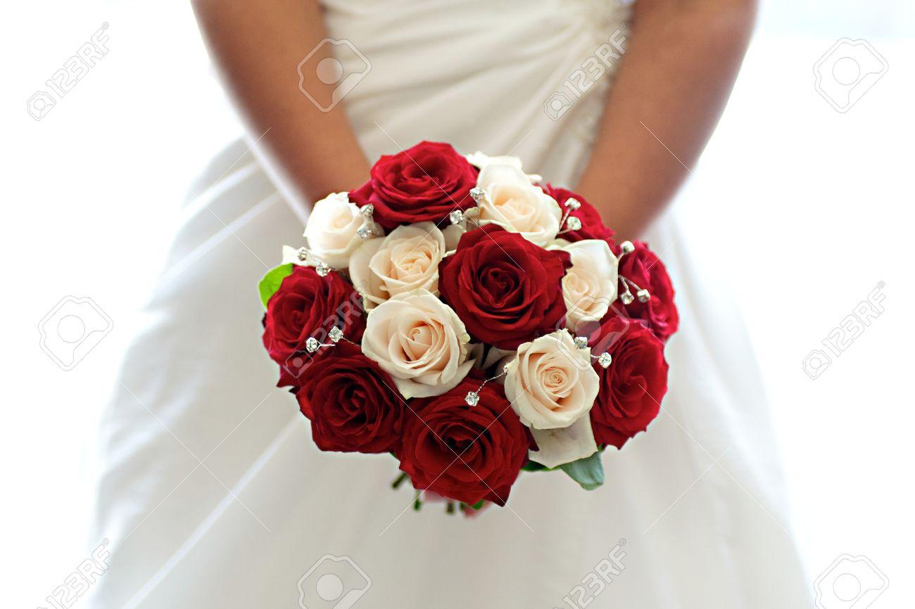 Foto de archivo , Hermoso ramo de rosas rojas y blancas en manos de una novia
