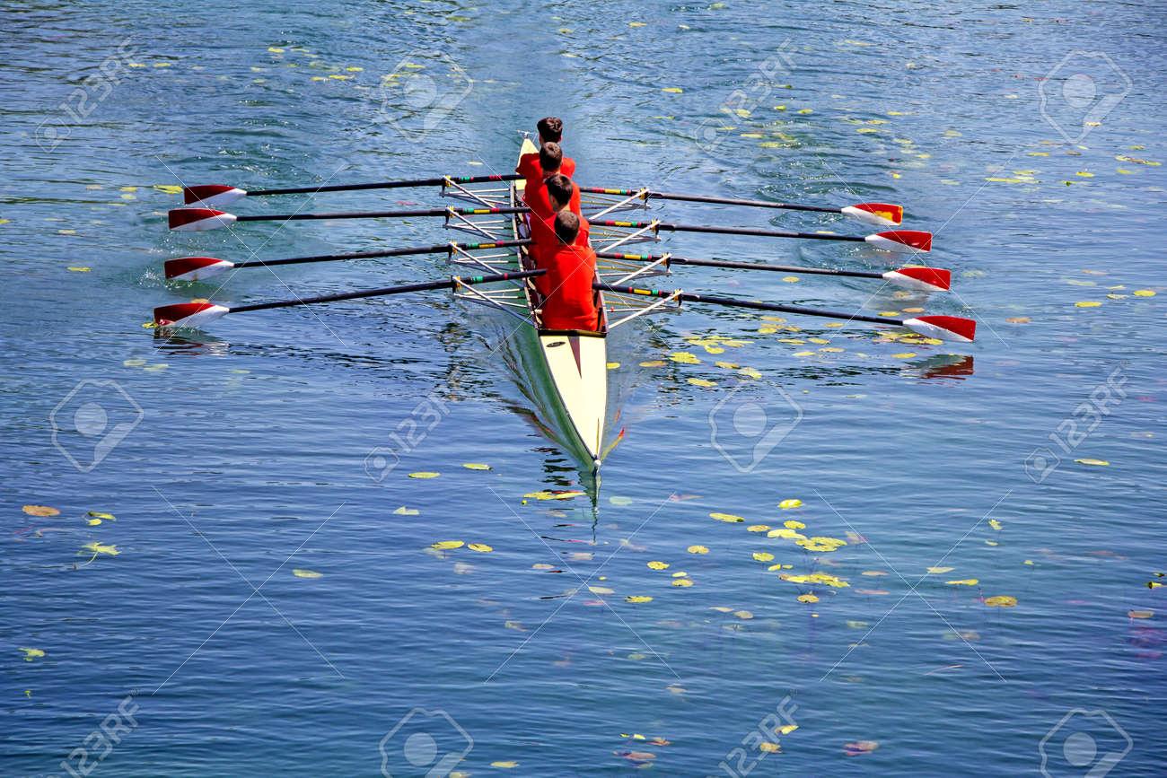 Men's quadruple rowing team on blue water, top view - 130798547
