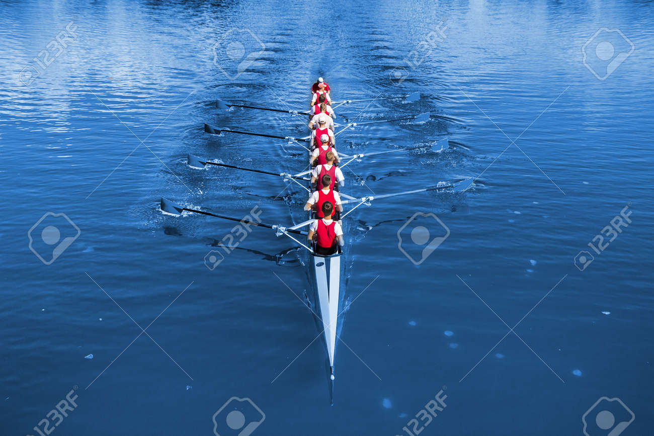 Boat coxed eight Rowers rowing on the blue lake. - 143163582