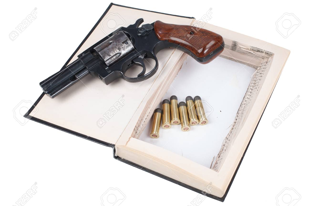 Revolver gun with cartridges hidden in a book isolated on white