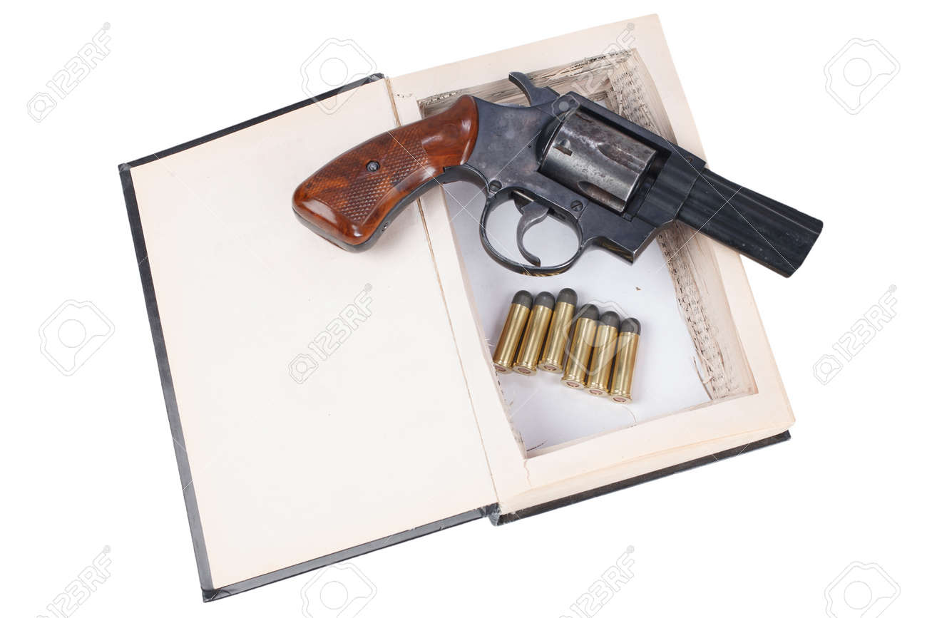38 caliber revolver gun with cartridges hidden in a book isolated