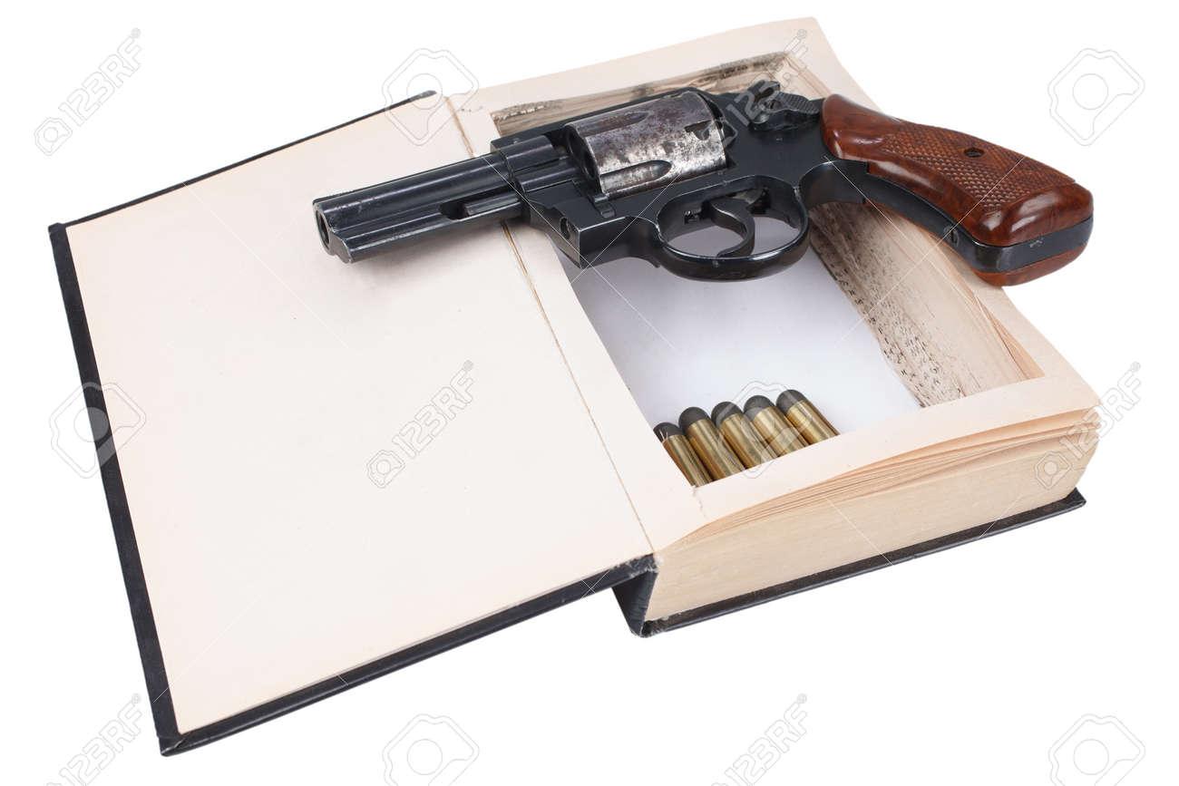 38 caliber revolver gun with cartridges hidden in a book isolated