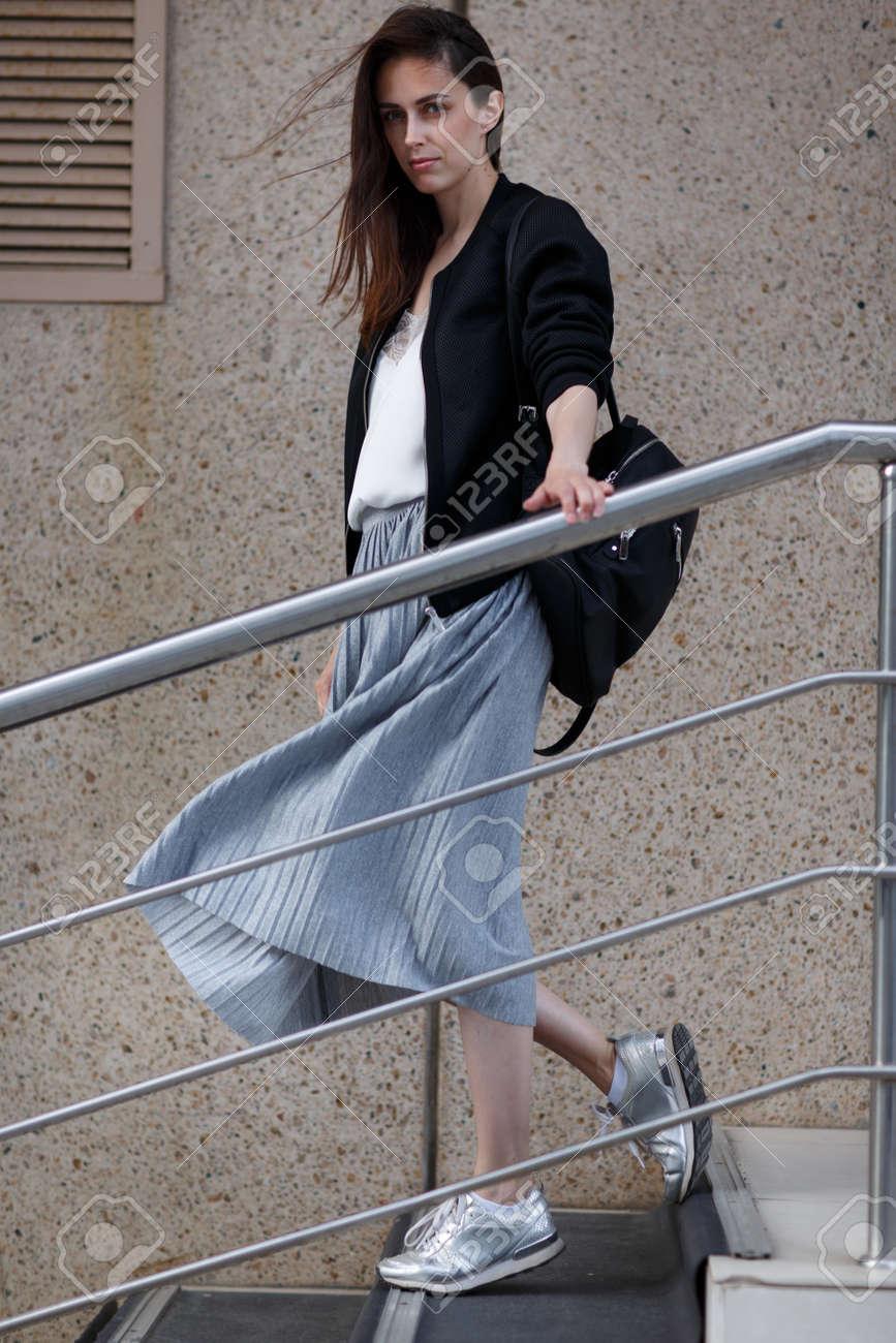 Archivio Fotografico - Brunette giovane donna in gonna grigia e giacca nera  cammina giù per le scale in scarpe da ginnastica e con la borsa d83df03e05e
