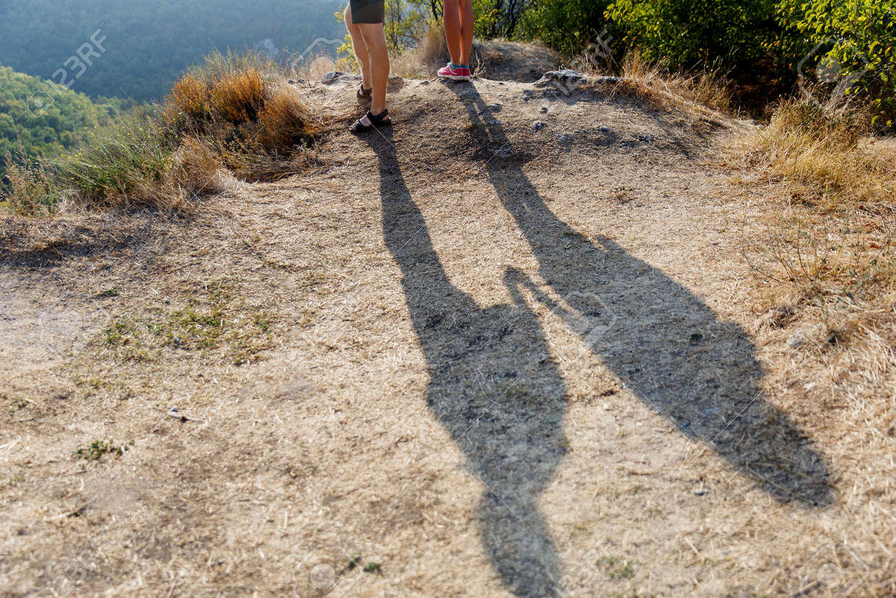 Shadow of two people holding hands on a hill with the sun-scorched grass  Stock 9e9907f7f4