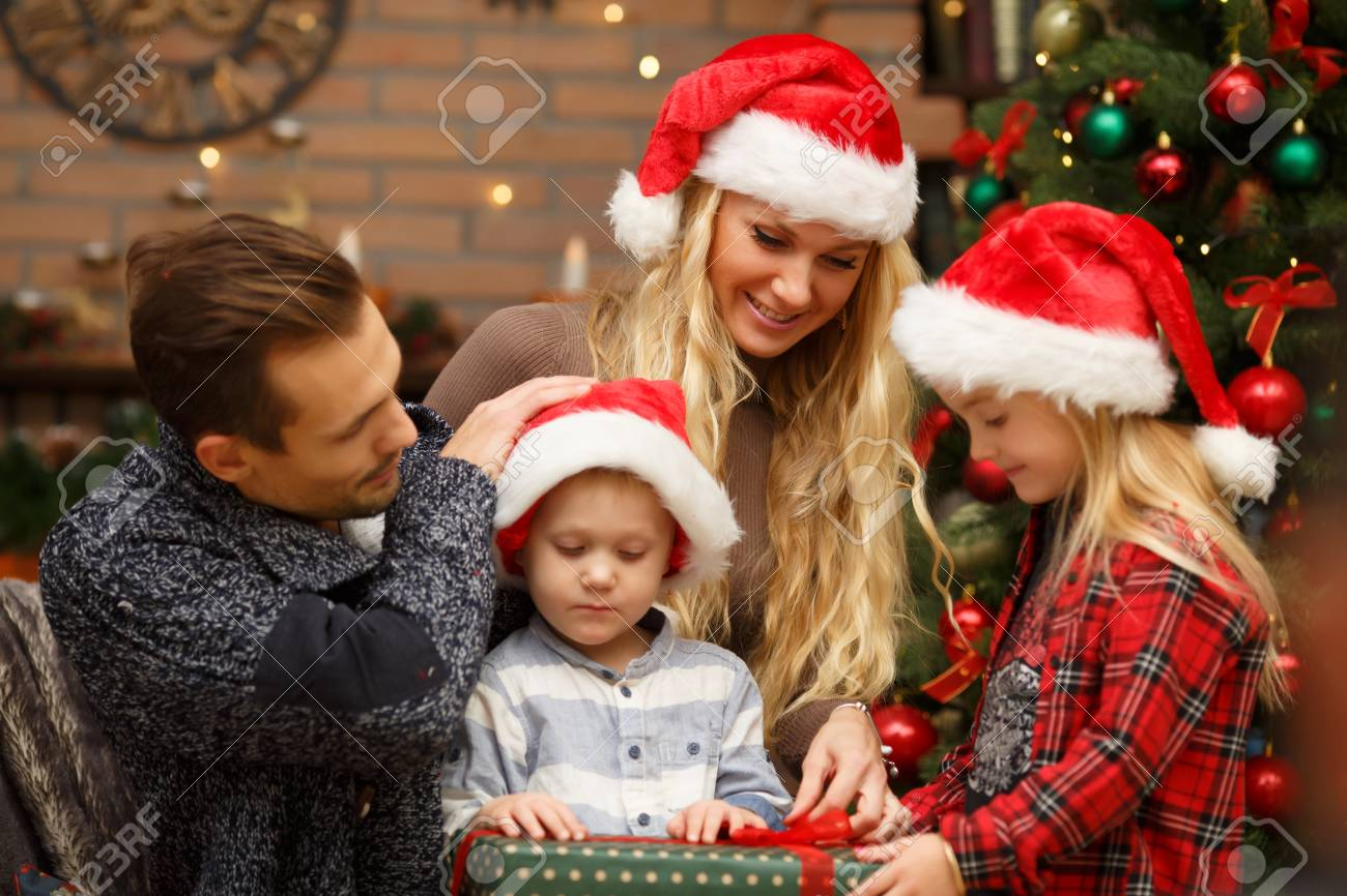 Christmas Hats For Kids.Young Family With Kids In Christmas Hats At Christmas Tree