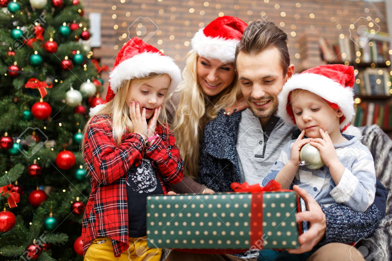 Surprised Children With Parents With Christmas Gifts At Christmas ...
