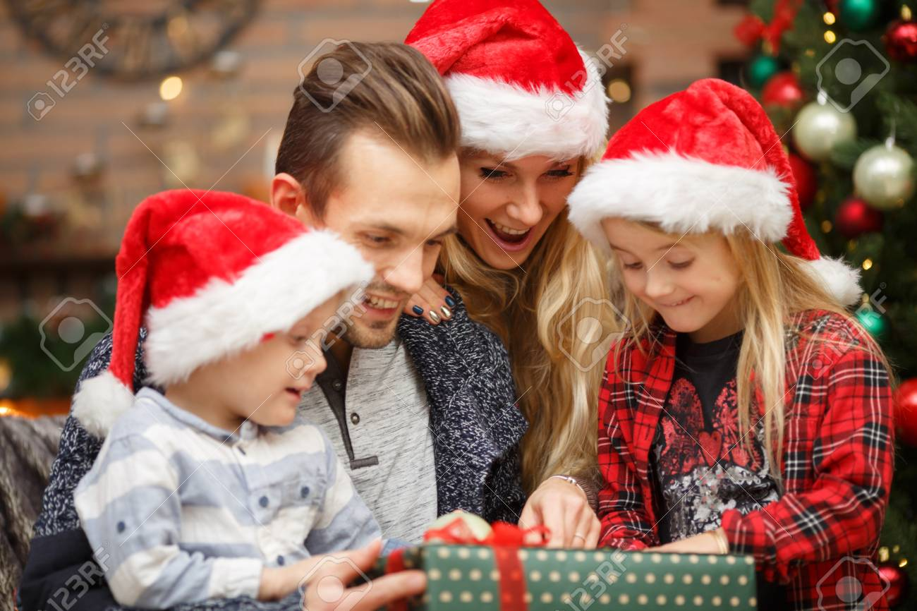 Christmas Gifts For New Parents.Young Parents With Kids Open Christmas Gifts