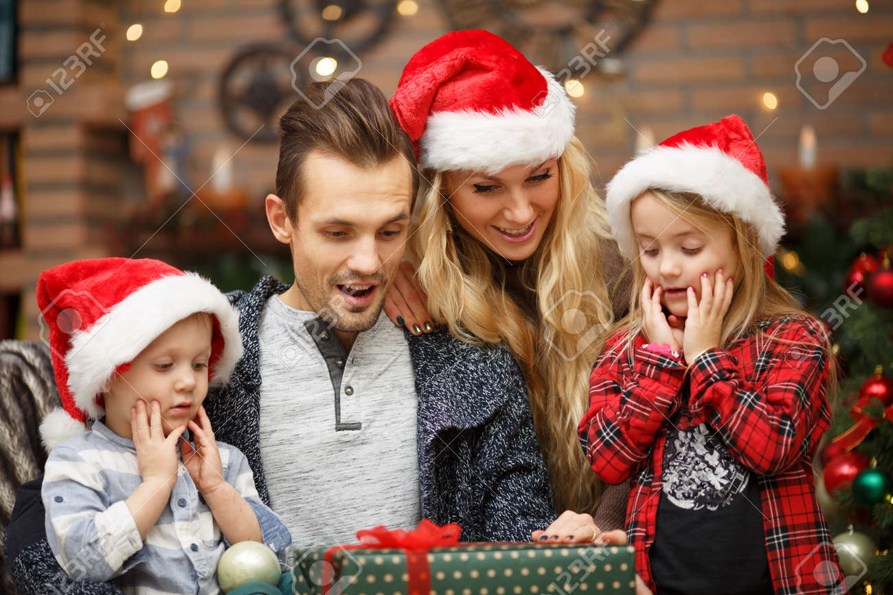 Surprised Family In Christmas Caps Open Christmas Gifts Stock Photo ...