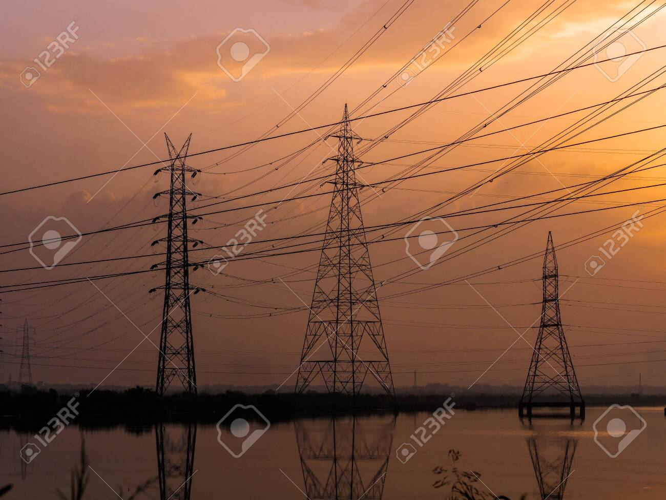 High-voltage power lines at Sunrise/sunset. electricity distribution station.Saltpans in Mumbai. - 156412991