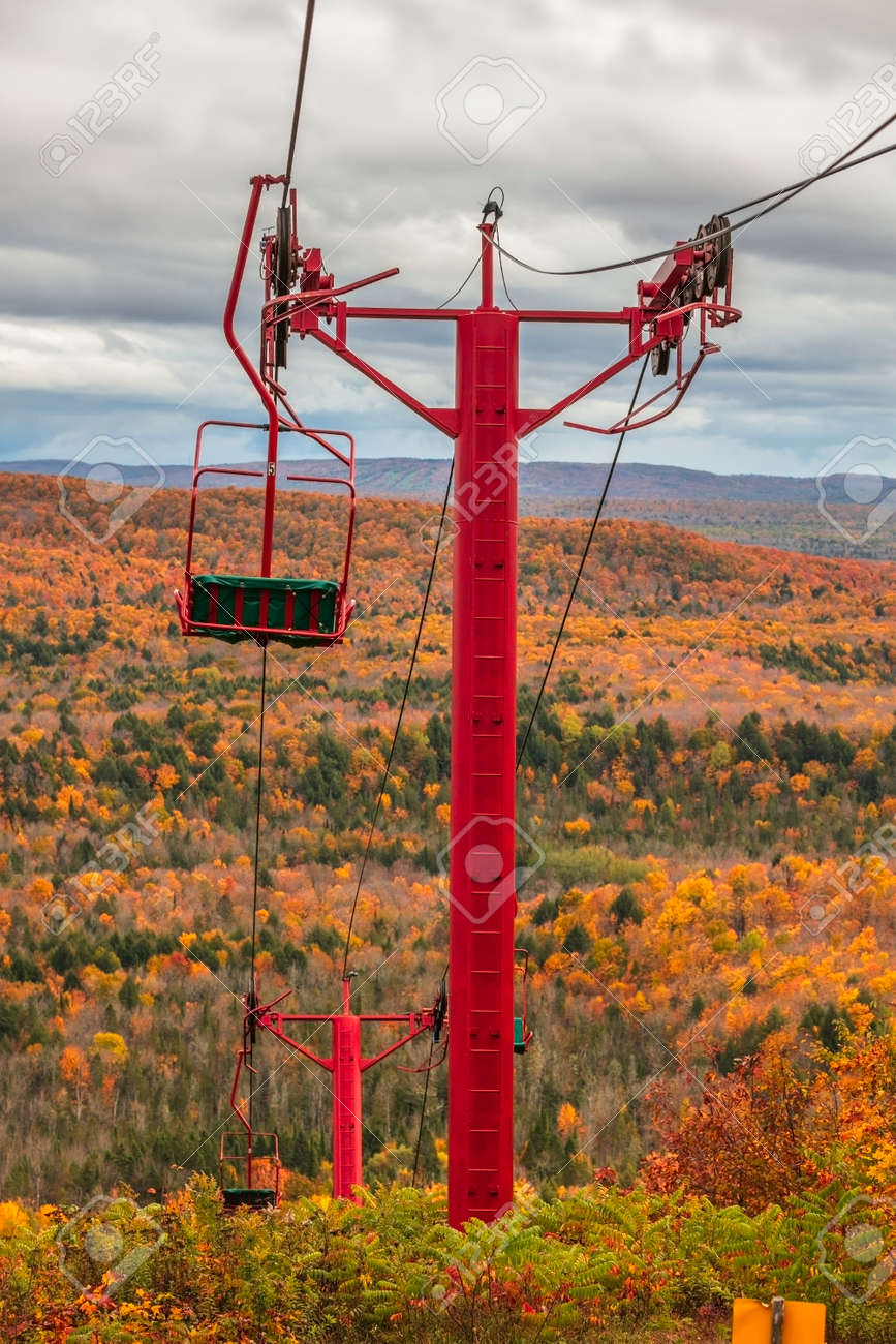 Cable chair lift tower at Copper peak in Michigan upper peninsula with sprawling Black river national forest foliage can be seen. - 164161302