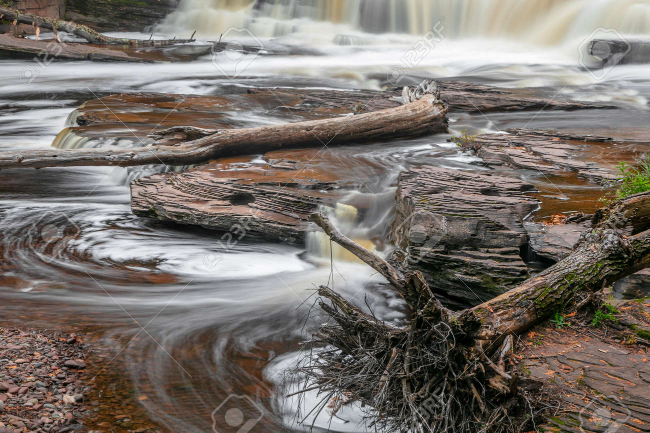 Running water over rocks at Manido falls with dead trees in the water in rural Michigan upper peninsula - 163023923