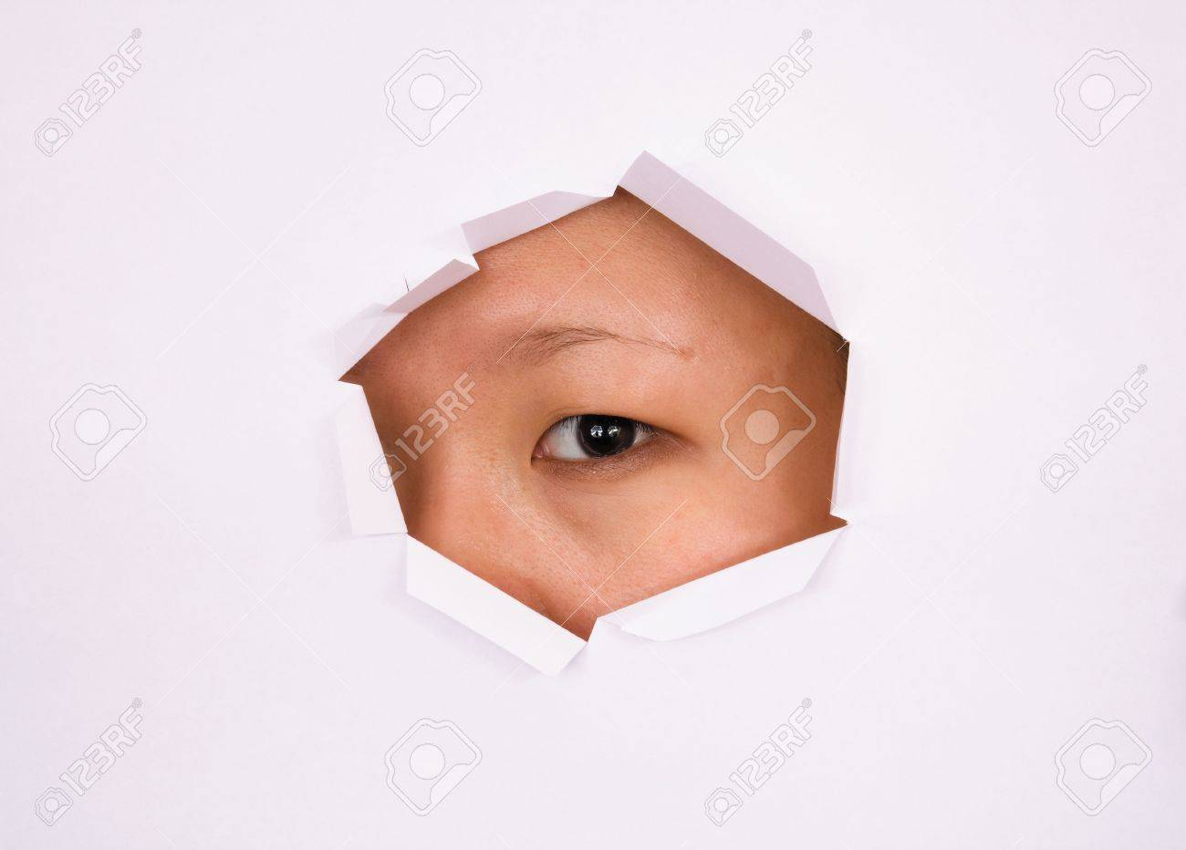 Eye looking through hole on paper surface Stock Photo - 3609244