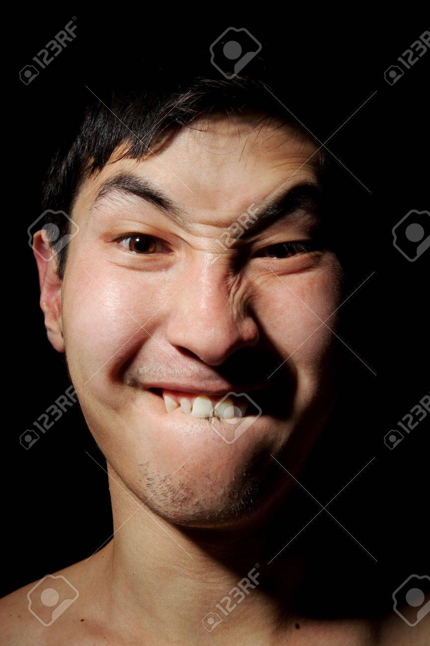 The obverse portrait of the young Asian man which has bitten a lower lip Stock Photo - 6596297