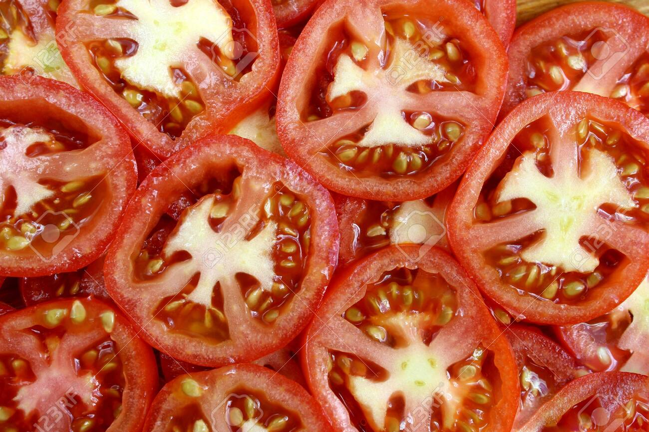 Ripe, red, juicy, sliced tomatoes are lying on the surface - 128386099