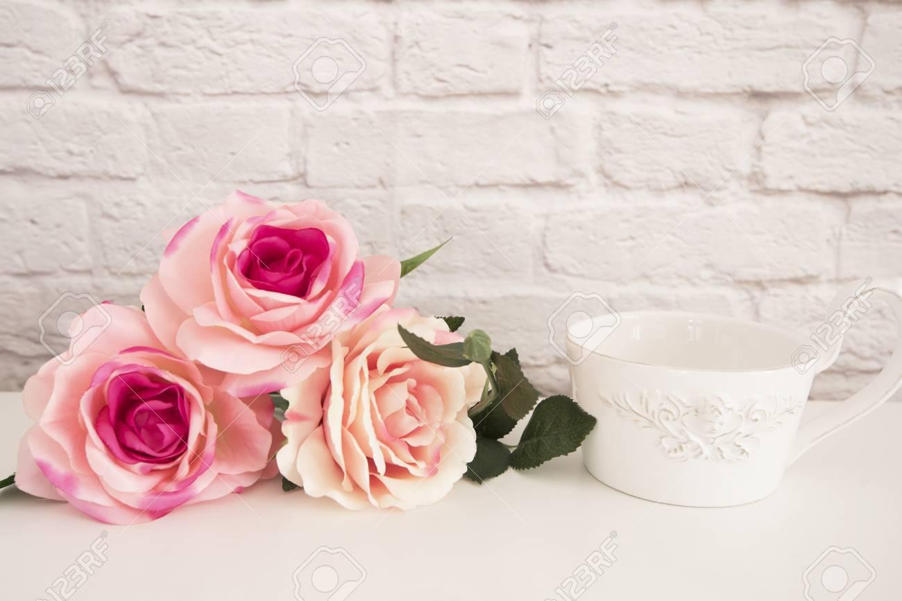 Bouquet de roses sur un bureau blanc une grande tasse de café