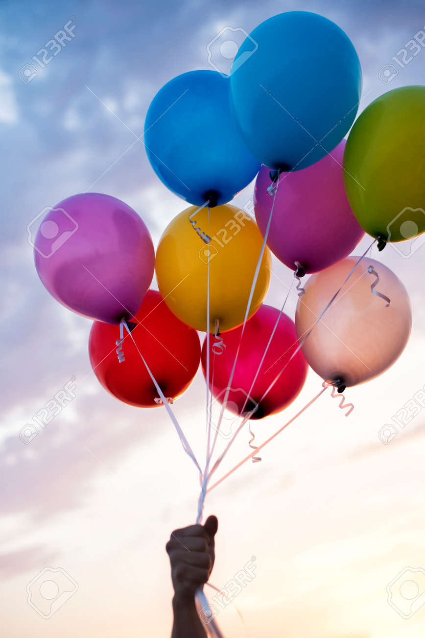 Man Hand Holding Colorful Balloons And A Beautiful Sunset Birthday Party Stock Photo