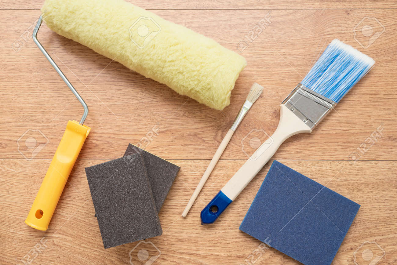 Painting brushes and rollers on wooden background  Building tools