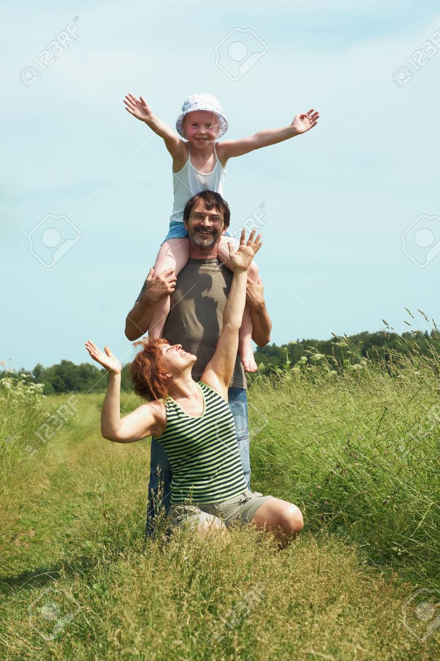 Parents with the daughter play on a meadow Stock Photo - 11641543