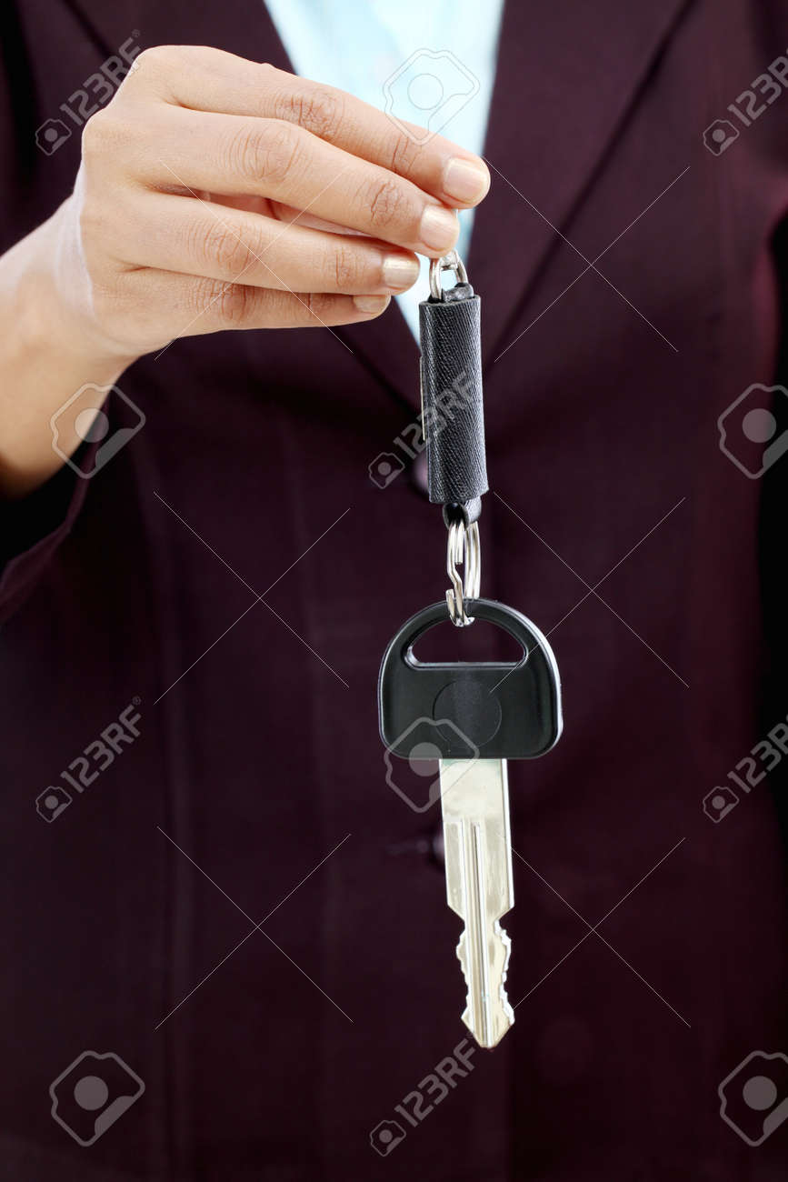 Happy young Indian business woman holding key against white background Stock Photo - 27649460