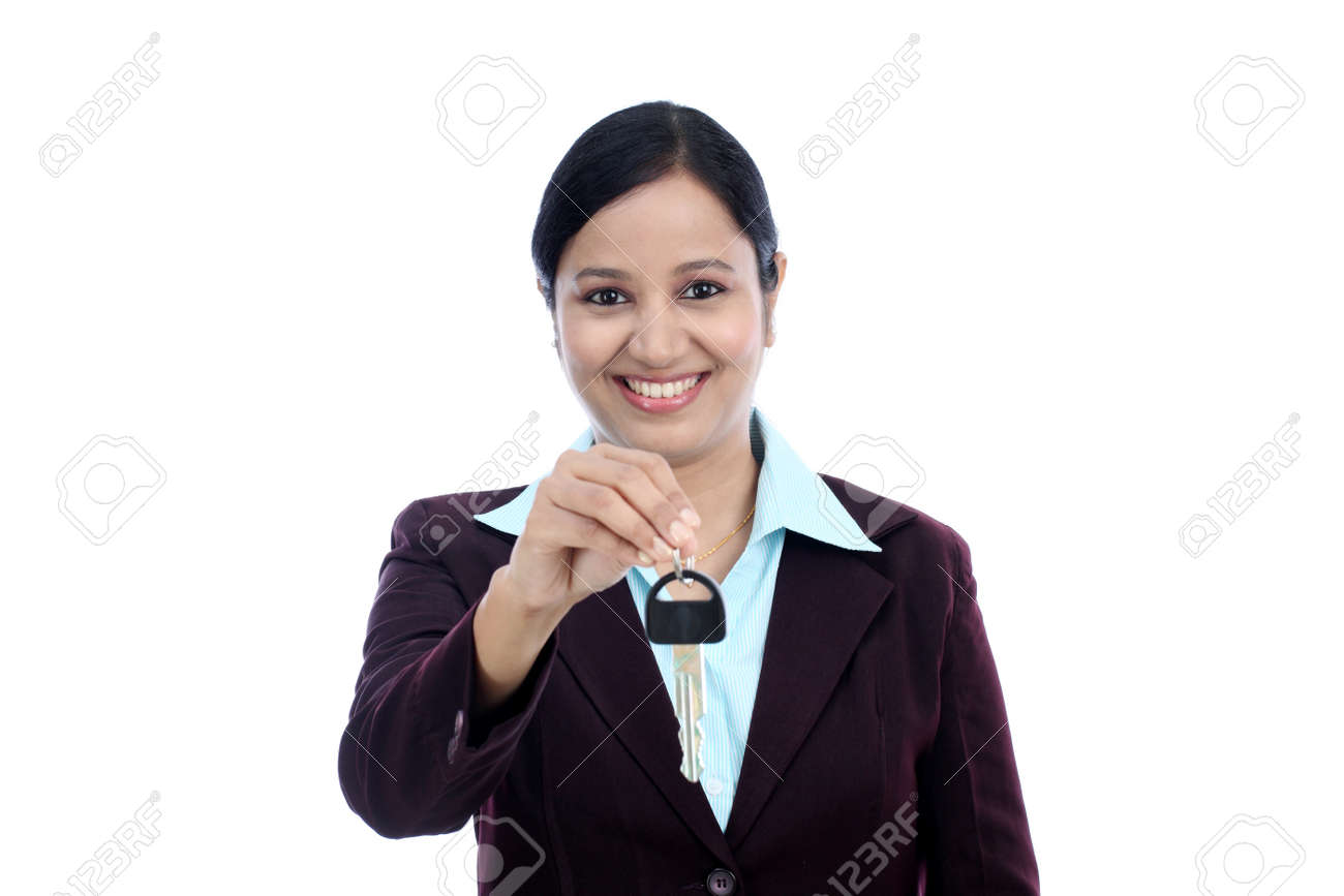 Happy young Indian business woman holding key against white background Stock Photo - 27743943