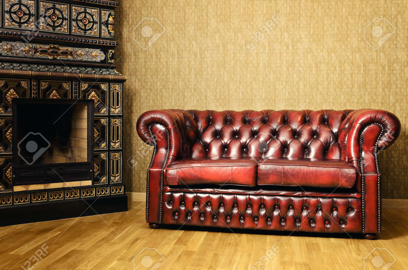Old Red Genuine Leather Sofa Near The Fireplace