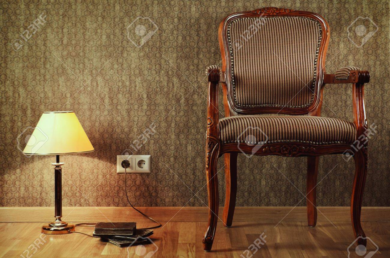 Old Armchair, Desk Lamp And Books On The Floor Stock Photo   18543470
