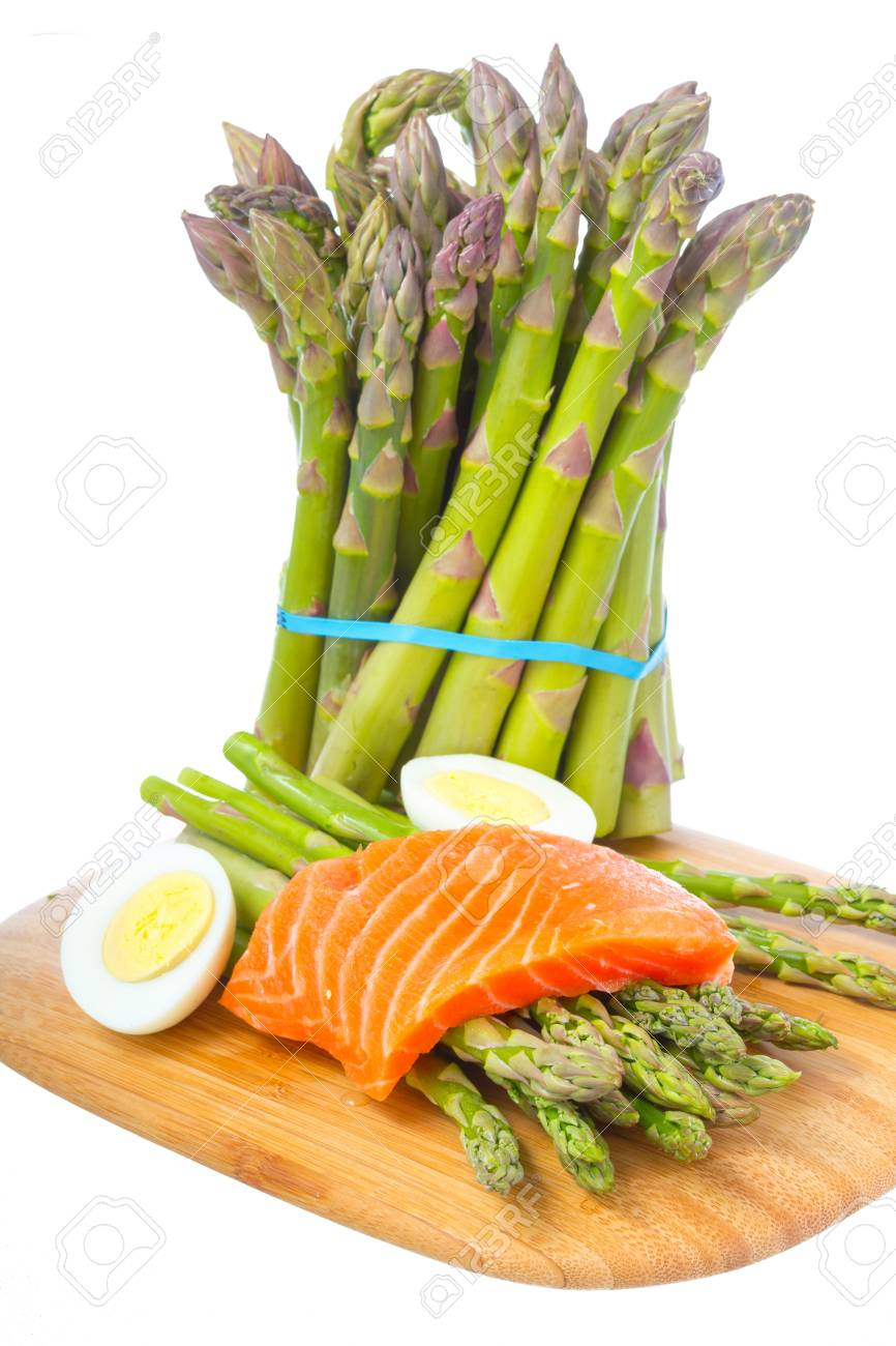 Fresh asparagus, boiled egg and raw salmon fillet on cutting board isolated on white background Stock Photo - 18943225