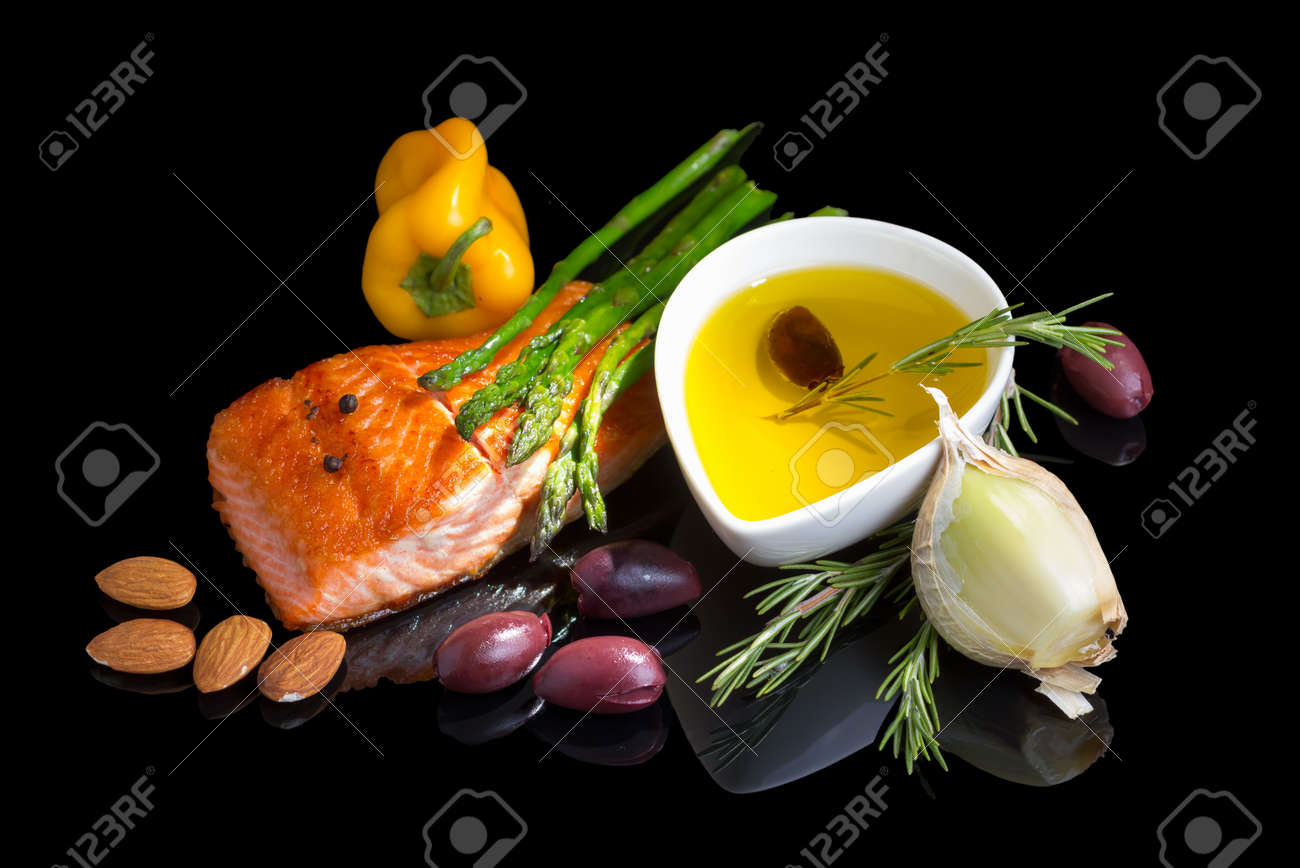Mediterranean omega-3 diet. Fish steak, olives, nuts and herbs isolated on black background with reflection. Stock Photo - 21982623