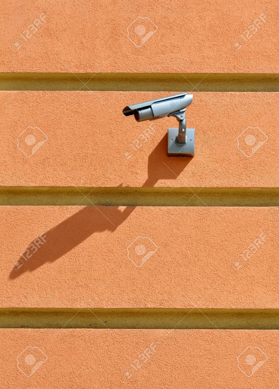 CCTV camera surveillance on the striped pink stucco wall watch left Stock Photo - 17399863