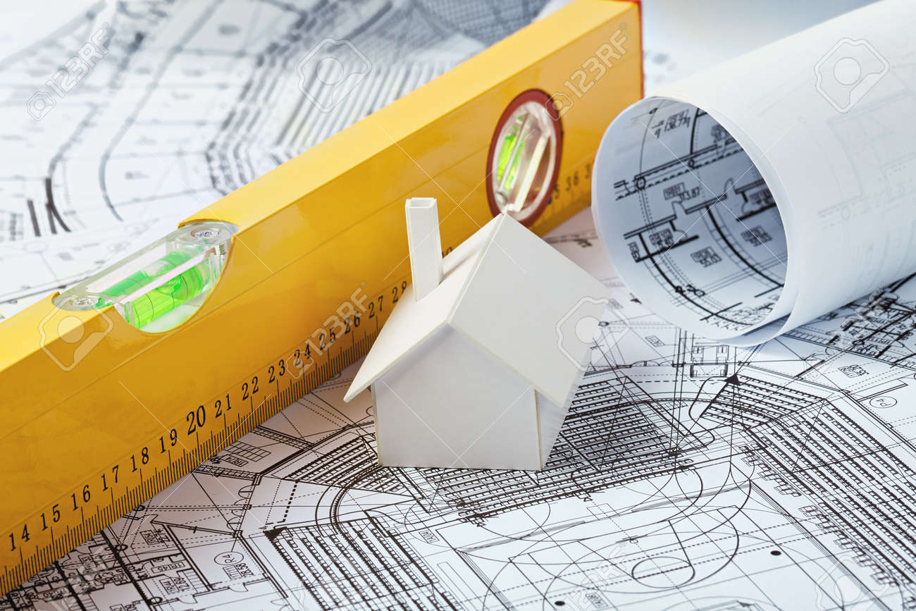 Small simple white model house on prints with a yellow leveler Stock Photo - 12954603