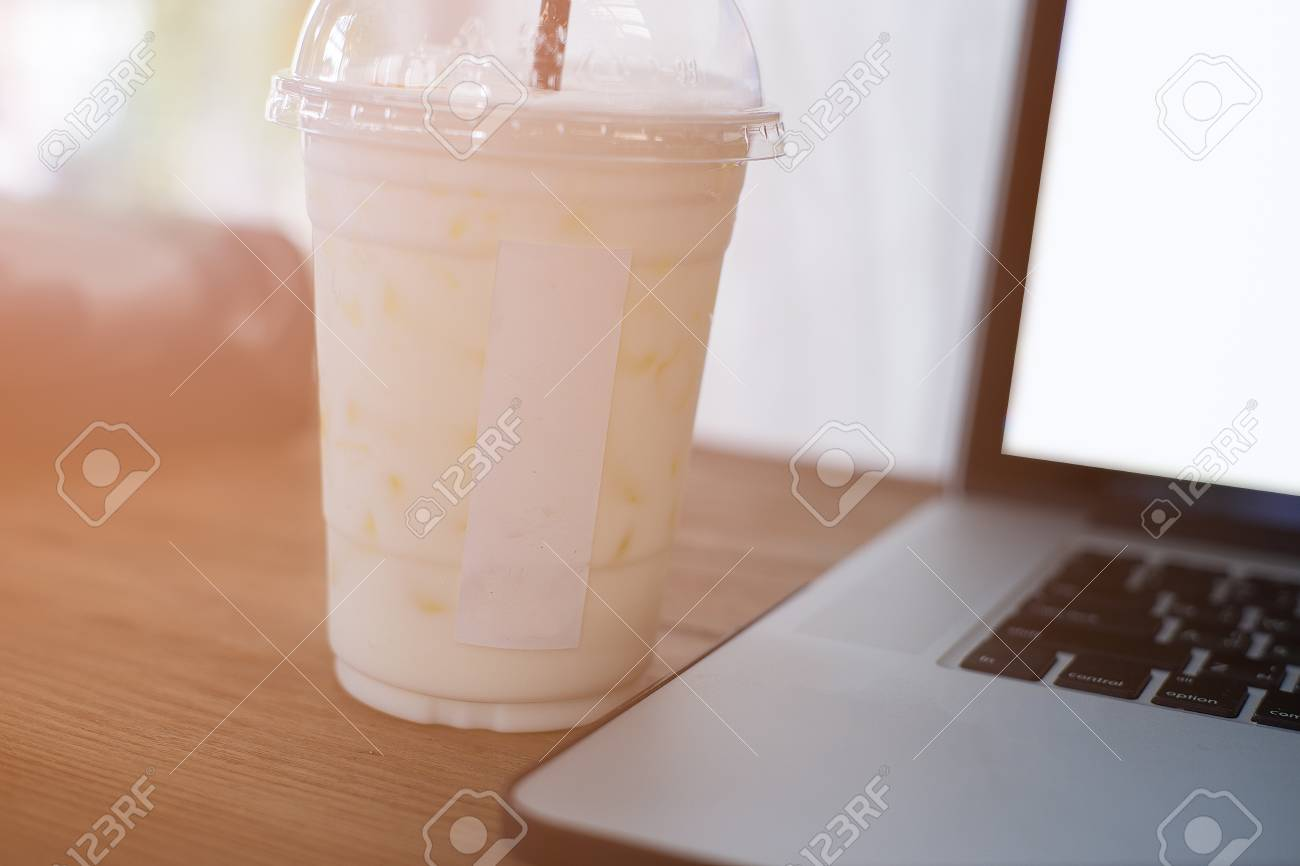 Cool ice milk in plastic glass with laptop on wooden table in