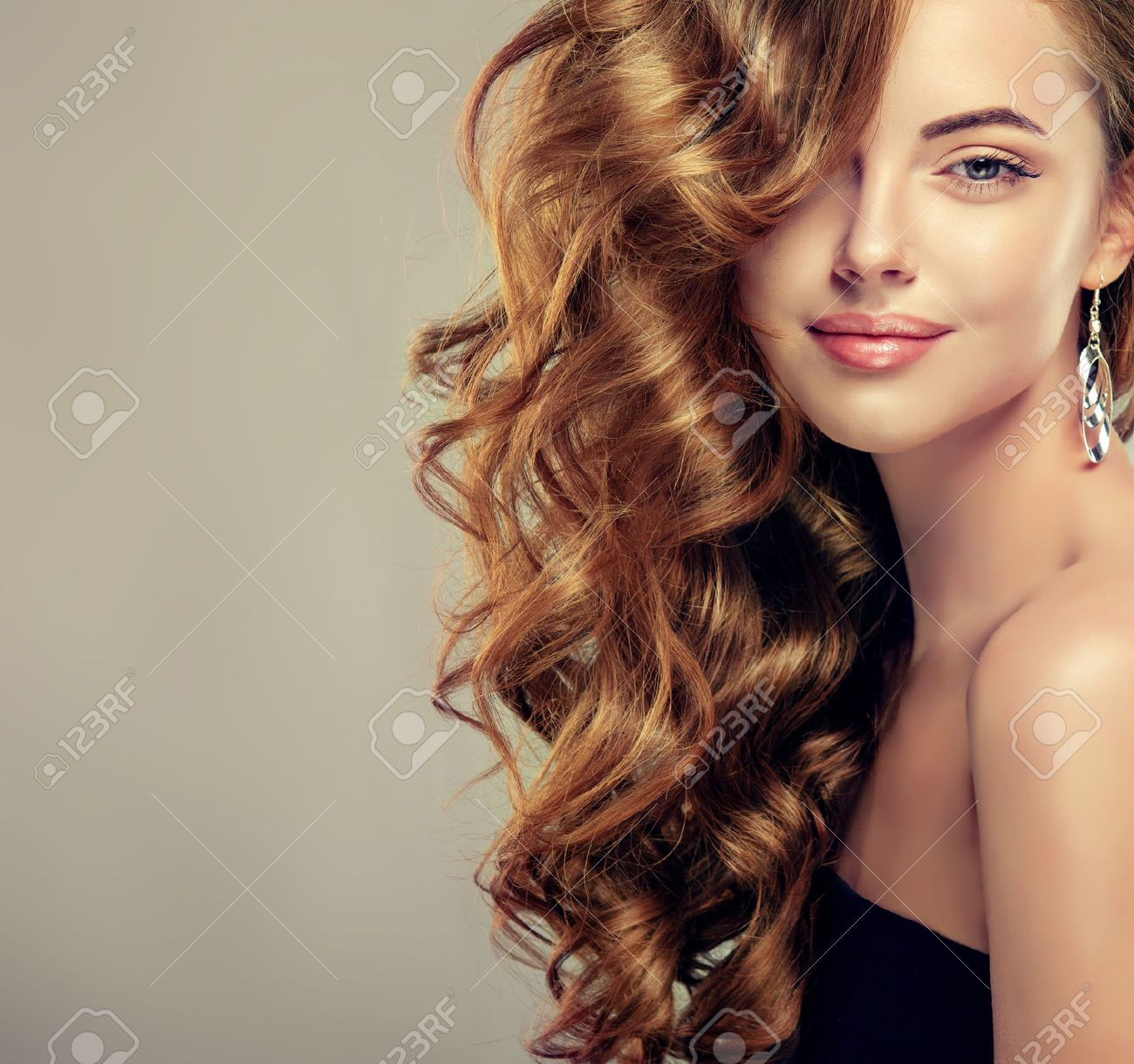 Beautiful girl with long wavy hair . Brunette model with curly hairstyle - 53032295