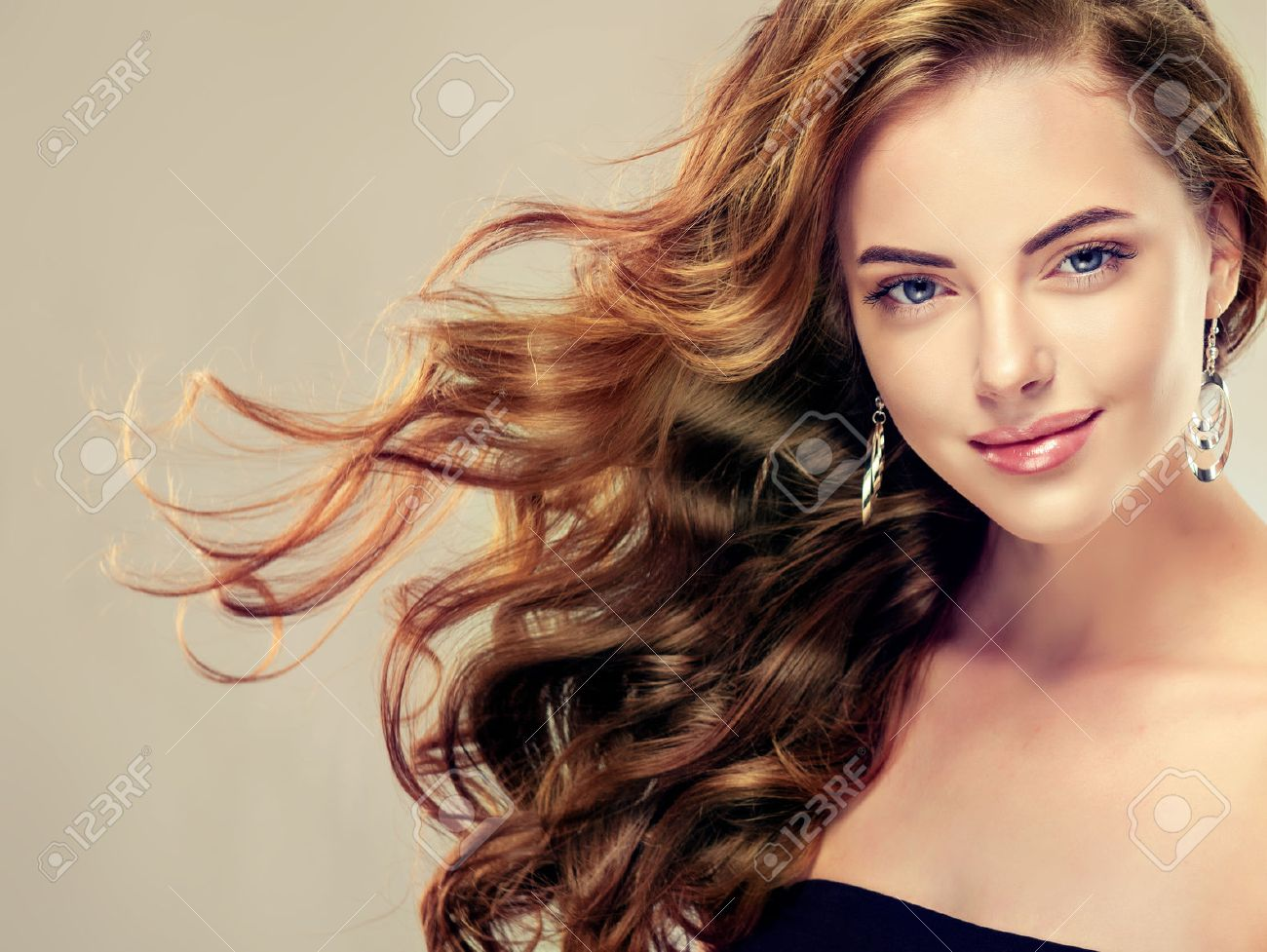 Beautiful girl with long wavy hair . Brunette model with curly hairstyle - 53032296