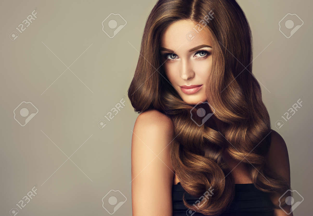 Brunette girl with long and shiny wavy hair . Beautiful model with curly hairstyle . - 62540848