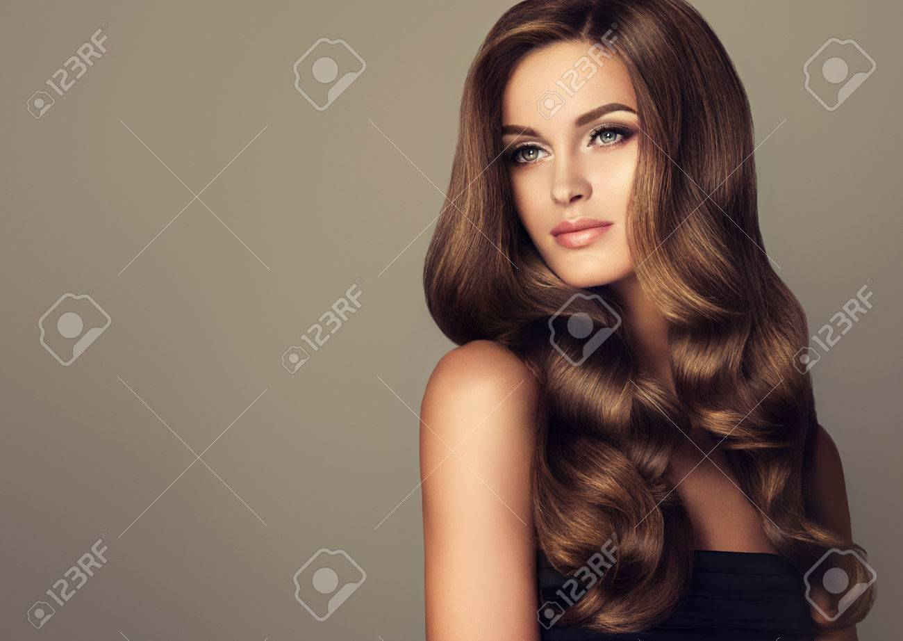 Brunette girl with long and shiny wavy hair . Beautiful model with curly hairstyle . - 62540849