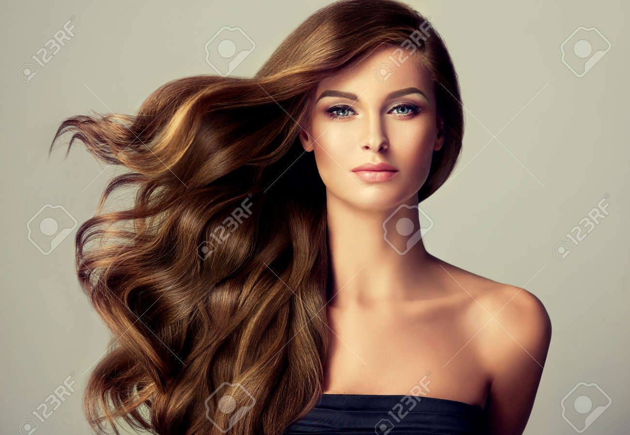 Brunette girl with long and shiny wavy hair . Beautiful model with curly hairstyle . - 62540851
