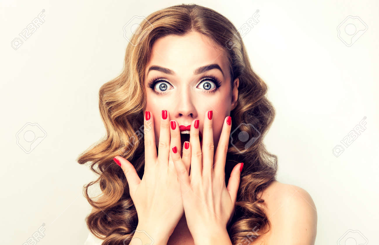 Facial expression of young woman displaying shock, astonishment and amazement. Beautiful girl with curly hair, perfect mack up and manicure. - 66704528