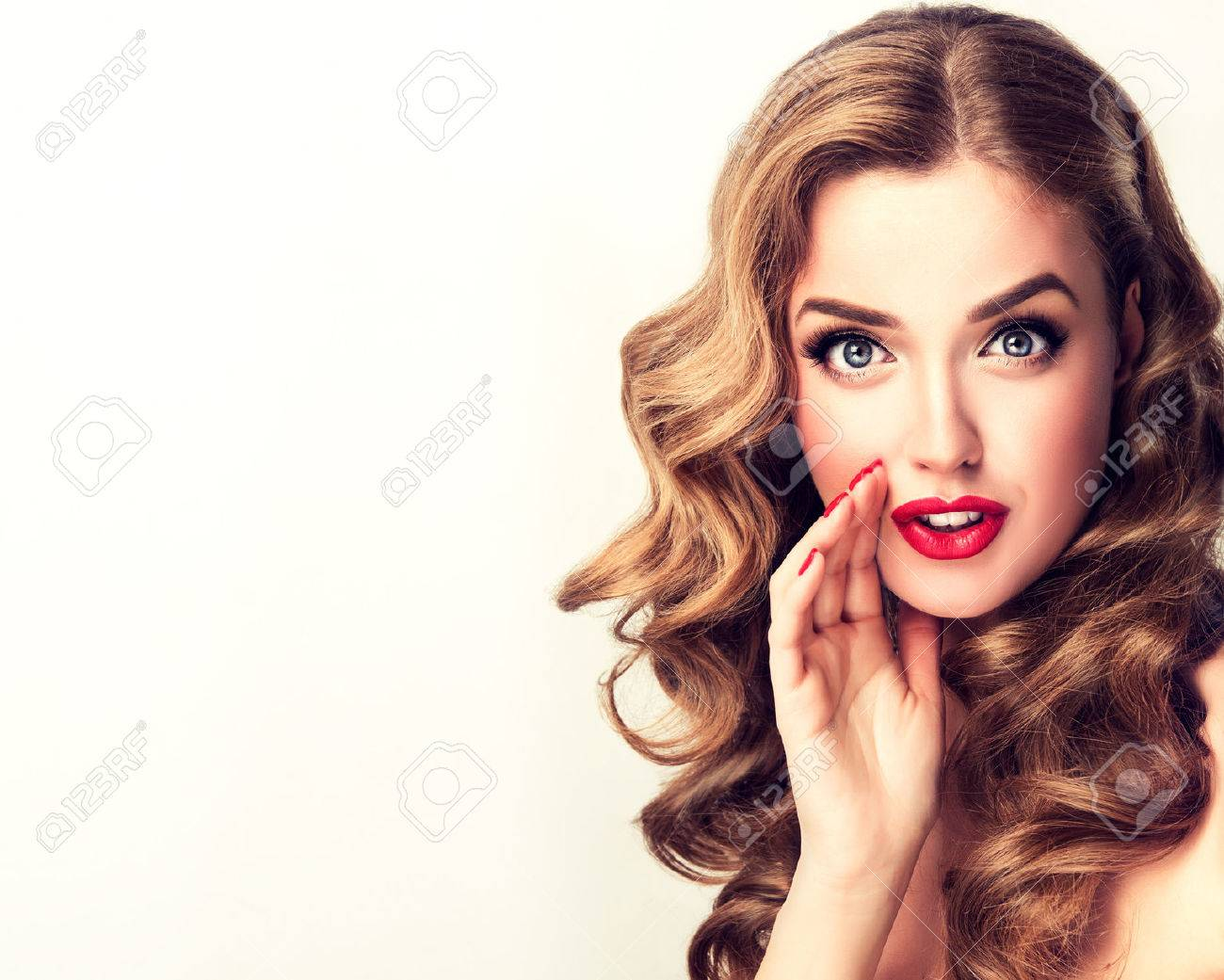 Beautiful girl with bright makeup and curly hair telling a secret. Expressive facial expressions. - 66637285