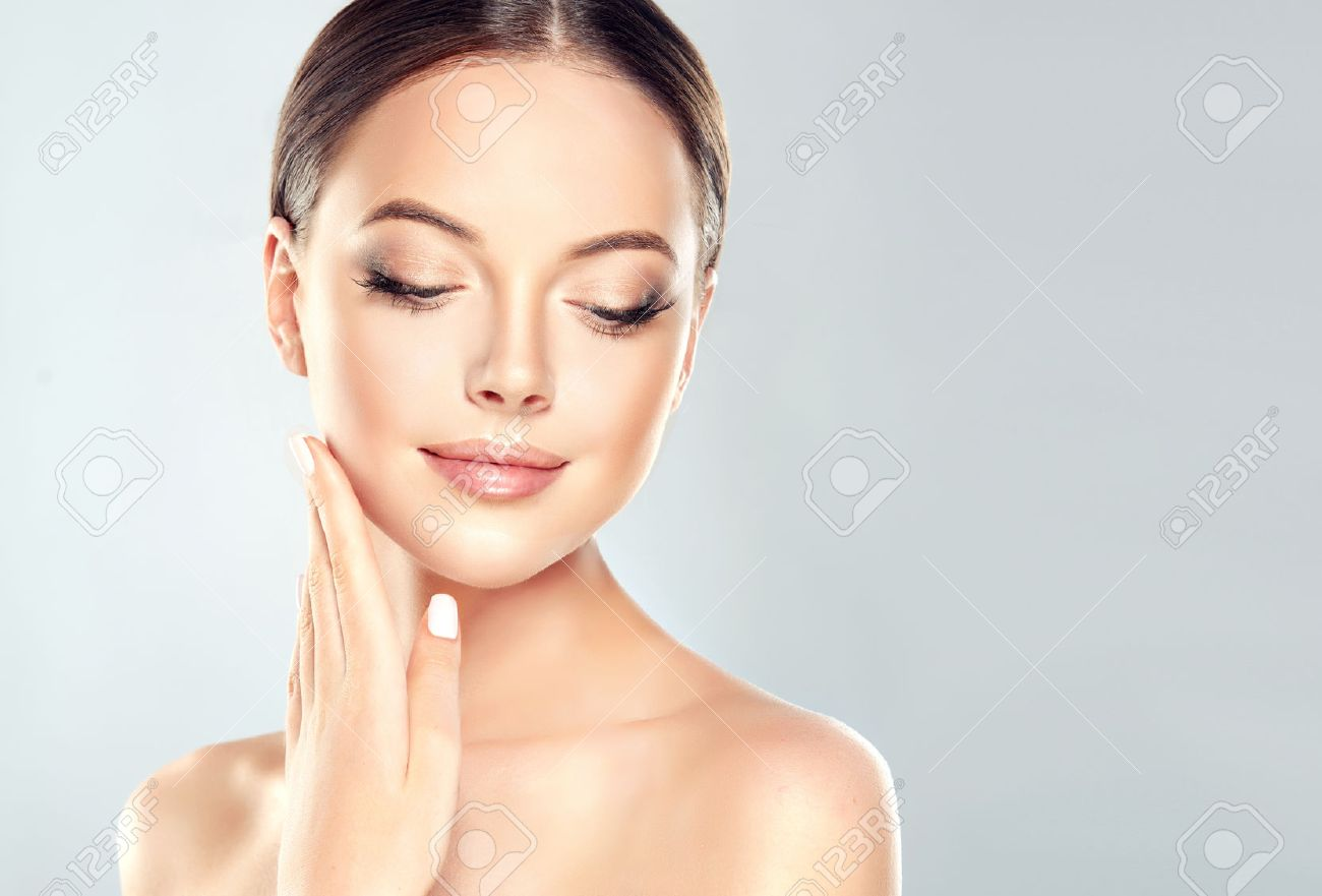 Beautiful Young Woman with Clean Fresh Skin touch own face . Facial treatment . Cosmetology , beauty and spa . - 73594766