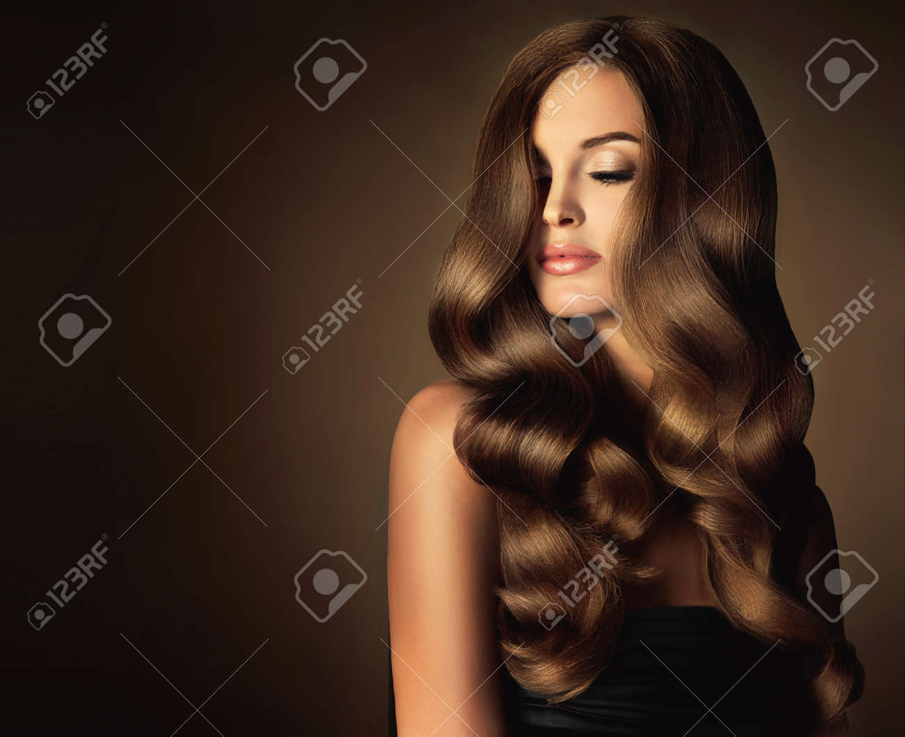 Brunette girl with long and shiny wavy hair . Beautiful model with curly hairstyle . - 72063180