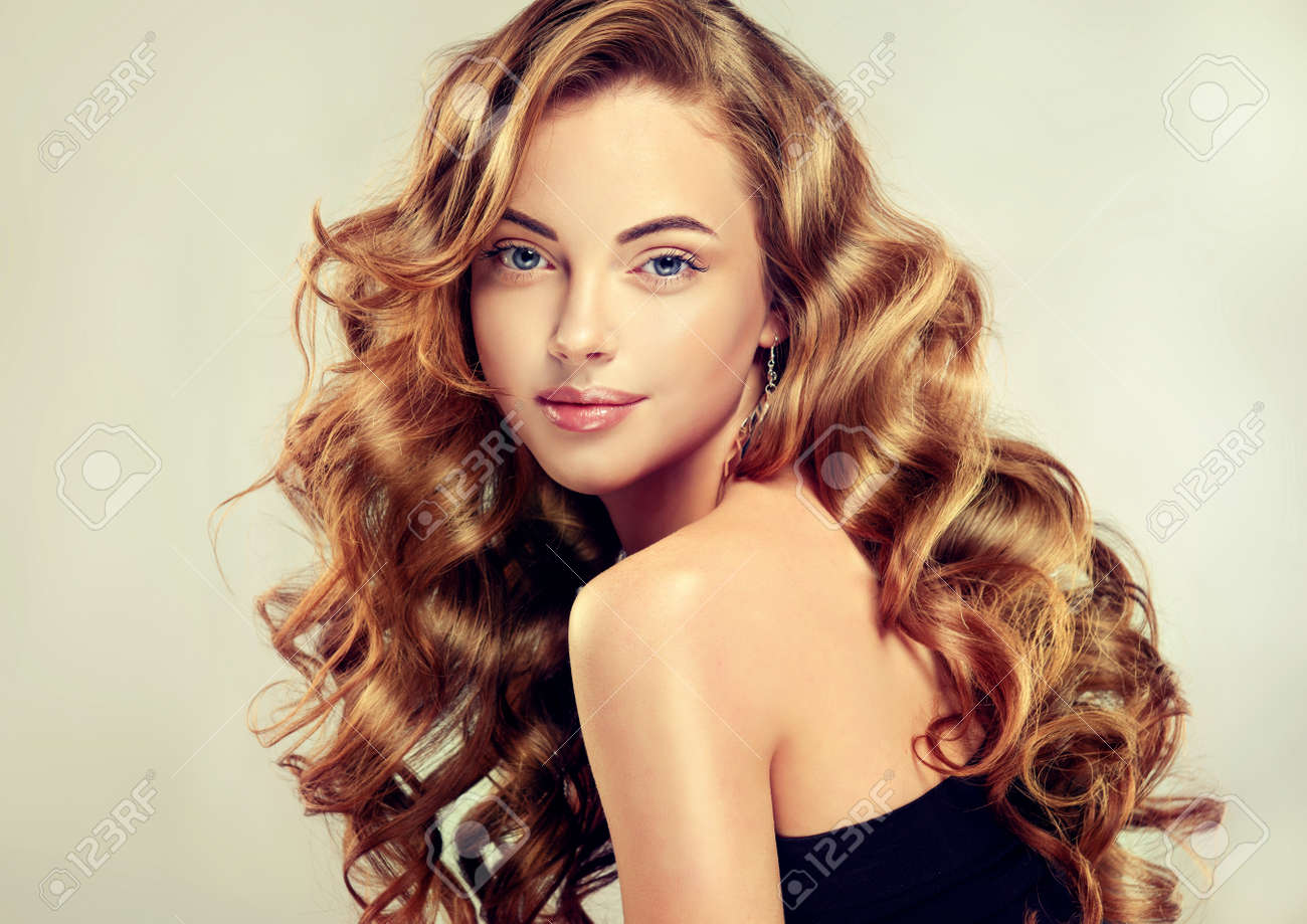 Voluminous hairstyles for long hair - Young Brown Haired Woman With Voluminous Shiny And Wavy Hair Beautiful Model With