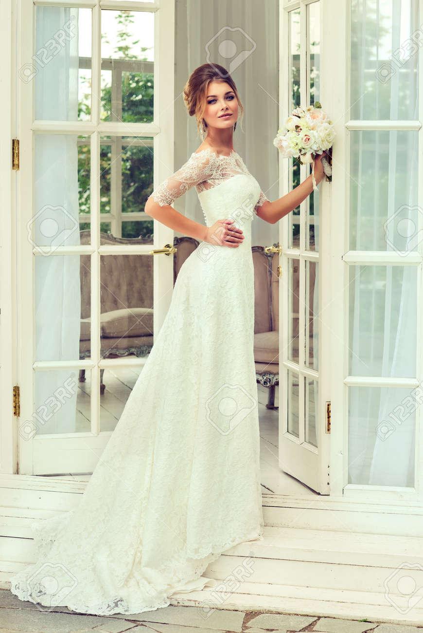 Mariée à La Mode Dans La Robe De Mariée Magnifique Et Chic Avec Bouquet De  Fleurs De Mariage. Coiffure De Mariage Parfait Pour Les Cheveux Longs,